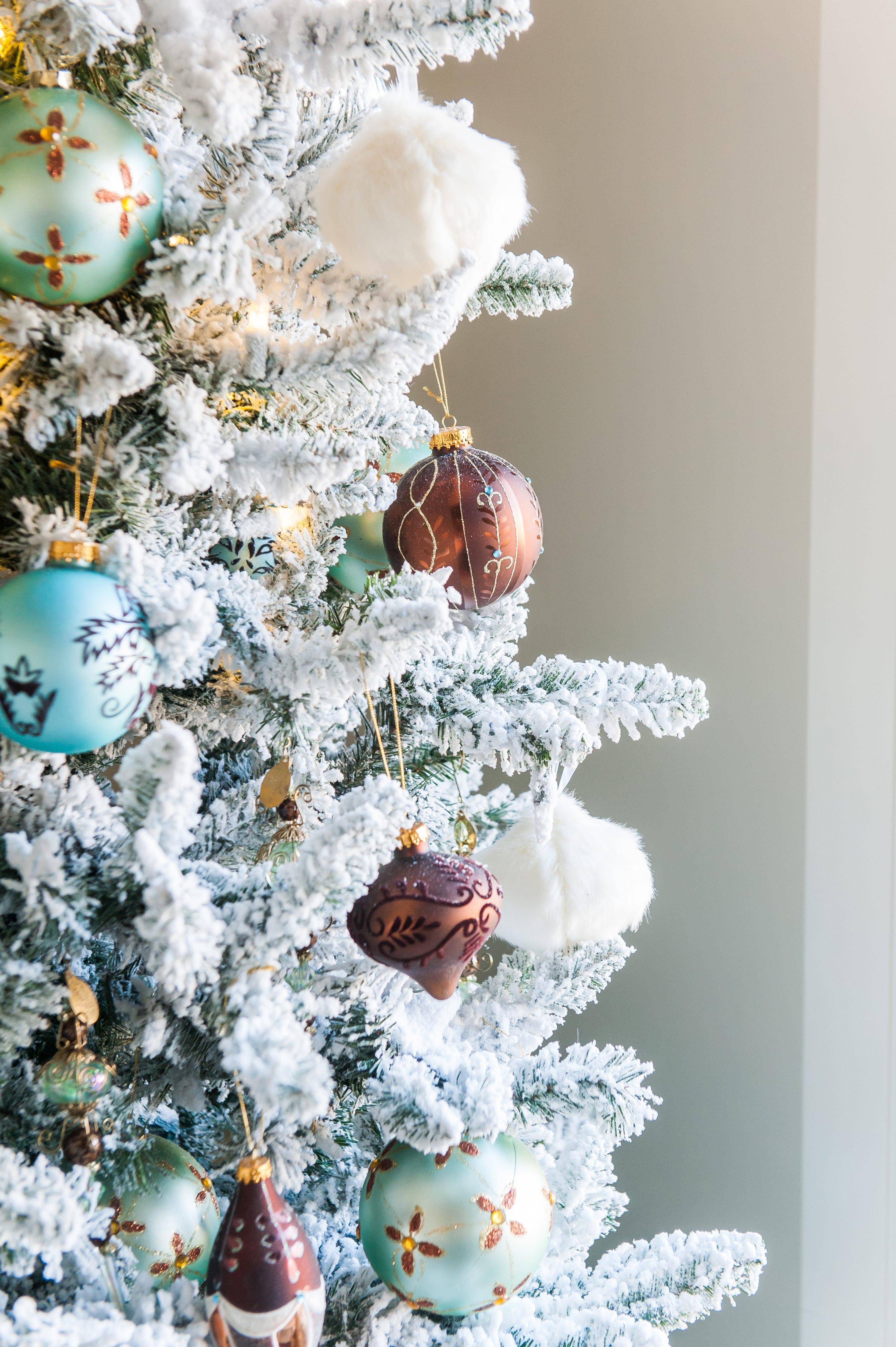 Christmas tree flocked long needle pine christmas tree flocked tree blue decor blue christmas ornaments trimming the tree shades of blue on white blue and cream flocked long needle pine artificial tree blue white ivory cream silver ornaments plaid ribbon